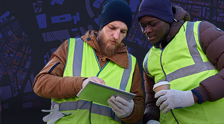 Two men in safety vests looking at a tablet