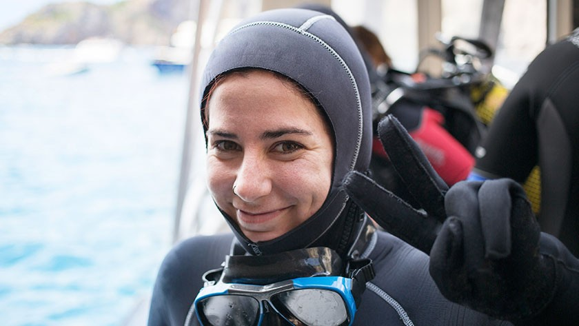 Woman in scuba gear smiling and holding up the hand sign for peace