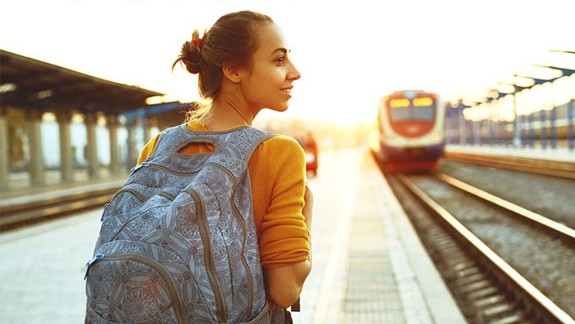 Woman wearing a backpack waiting at a train station